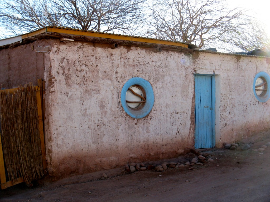 A house with windows made of tires. The glass appeared to be a washing machine door. Bars are sticks embedded in adobe. Beautiful and practical! Photo: Steve Peterson